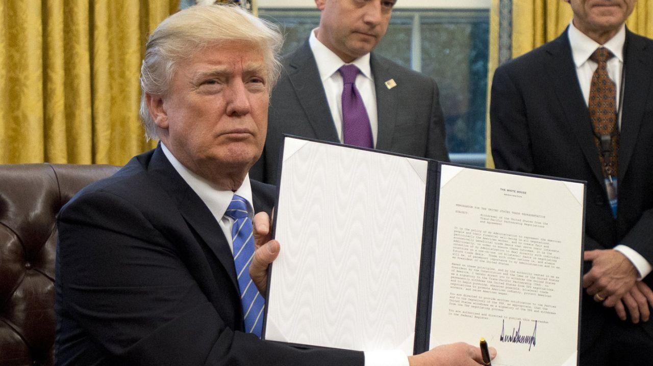 Prezident USA Donald Trump ukazuje médiím podpis pod listinou o odstoupení od smlouvy TPP. Zdroj: Reuters.com